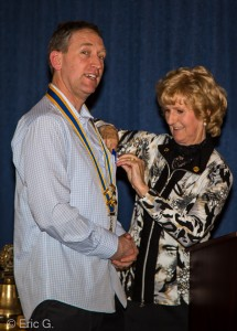 Muriel Heron pins the Presidents badge onto Andrew Goldsworthy.